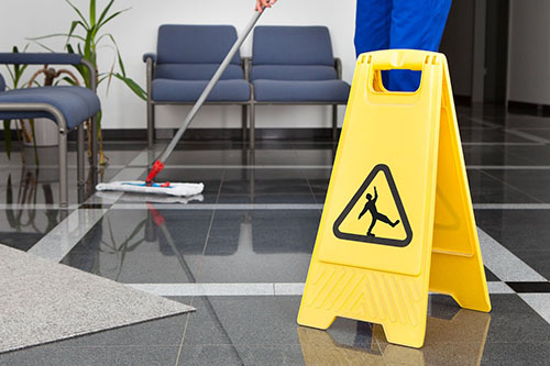 Person cleaning tiles floor with caution wet floor sign